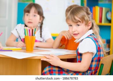 Two cute little girls drawing at kindergarten