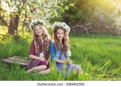Two cute little girls friends with wreath of flowers in a blooming apple orchard