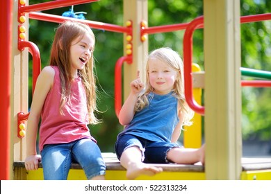 Two cute little girls having fun on a playground outdoors in summer