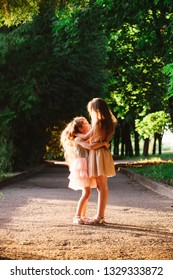 Two Cute little girls hugging and laughing at the garden at warm summer evening. Happy kids outdoors concept. Soft focused