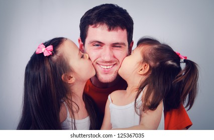 Two cute little girls kissing his happy dad