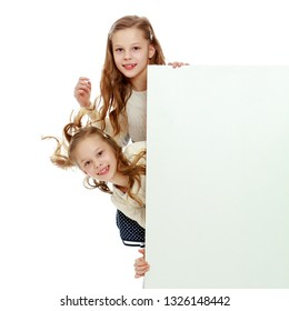 Two cute little girls look out from behind a white advertising banner. On the banner you can make any advertising inscription or put a picture or logo. It is isolated on a white background.
