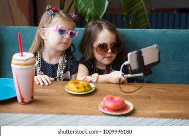 Two cute little girls making selfie in cafe
