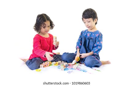 Two cute little girls playing with alphabet blocks isolated on white background. Development, progress and education concept or others your content. Selective focus.