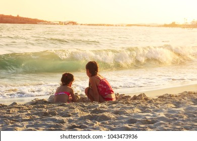Two Cute Little Girls playing with sand by the Sea Waves at sunset.  Summer Sunny Day, Ocean Coast, happy Kids concept