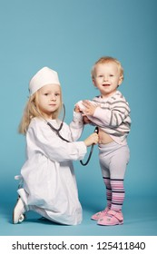 two cute little girls playing doctor. studio photo
