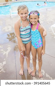 Two cute little girls playing together in their back yard swimming pool on a warm summer day