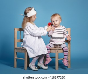 two cute little girls playing doctor
