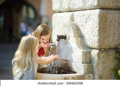 Two cute little girls playing with a drinking water fountain on warm and sunny summer day in Desenzano del Garda town in Italy