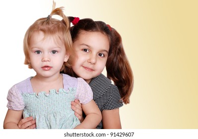 Two cute little girls portraits on light beige background