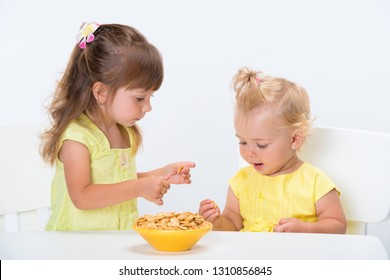 Two cute little girls sisters in yellow t-shirts eating cereal flakes at the table isolated on white background.