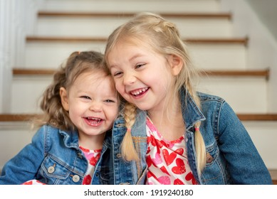 Two cute little girls sitting together at home laughing