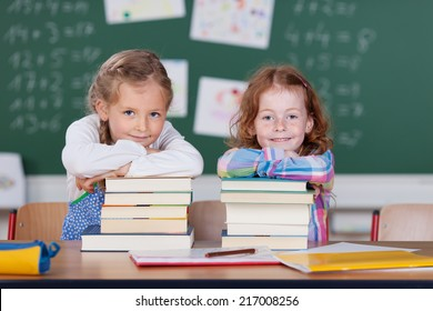 Two cute little girls with their school books stacked on a desk in front of the blackboard leaning on them smiling at the camera