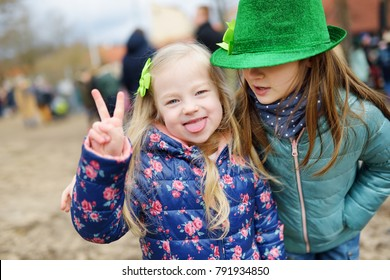 Two cute little girls wearing green hats and accessories celebrating St. Patrick's day in Vilnius. Children having fun at traditional irish festival.