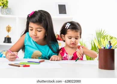 Two Cute little Indian/Asian little girls or siblings  enjoying colouring or drawing or painting using pastel colours or sketch pens at table at home