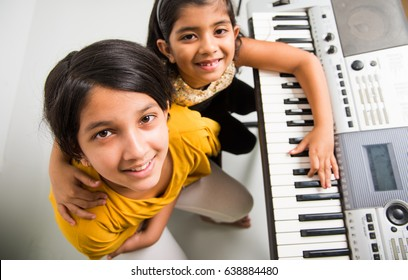 Two Cute little Indian/Asian girls playing piano or keyboard, a musical instrument, over white background