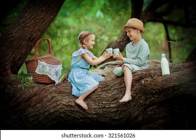 Two cute little kids sitting on a huge brunch of the tree and making up a picnic on a sunny summer day. Children in the country.