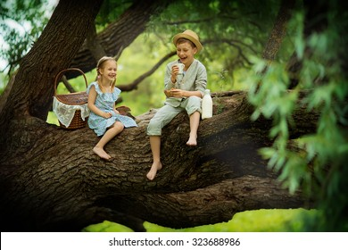 Two cute little kids sitting on a huge brunch of the old tree and making up a picnic on a sunny summer day. Children in the country.