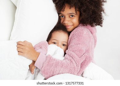 Two cute little sisters in bed
