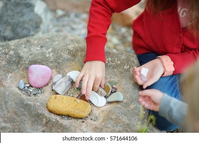 Two cute little sisters collecting beautiful stones on a pebble beach on summer day