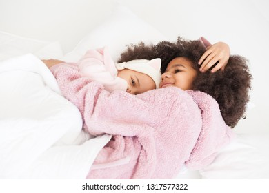 Two cute little sisters in cozy bed