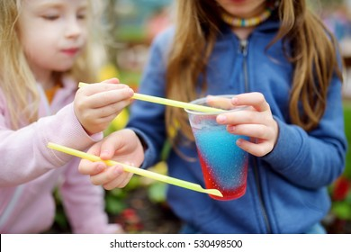 Two cute little sisters drinking colorful frozen slushie drink on hot summer day