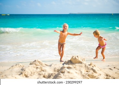 Two cute little sisters girls having fun on colorful tropical beach with turquoise water of ocean and white sand