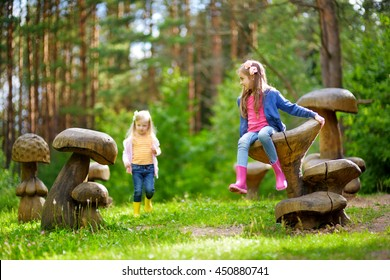 Two cute little sisters having fun on giant wooden mushrooms on a playground outdoors