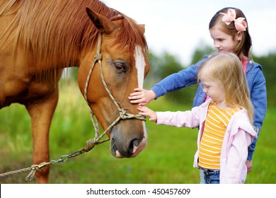 Two cute little sisters petting a horse in countryside on beautiful summer day