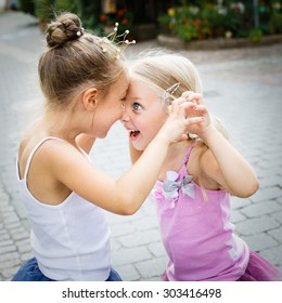 two cute little sisters, selective focus. The girl with dark hair is wearing a princess crown.