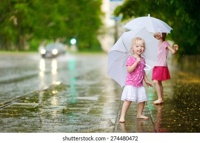 Two cute little sisters standing in a puddle holding umbrella on a rainy summer day