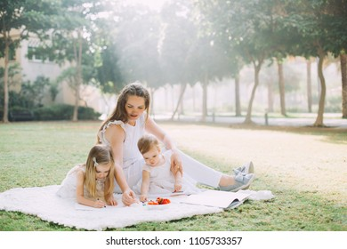 Two cute little sisters and their mother eating strawberries and drawing at summer picnic in park