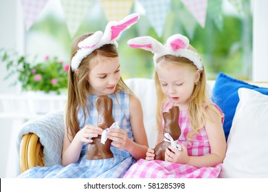 Two cute little sisters wearing bunny ears eating chocolate Easter rabbits. Kids playing egg hunt on Easter. Adorable children celebrate Easter at home.