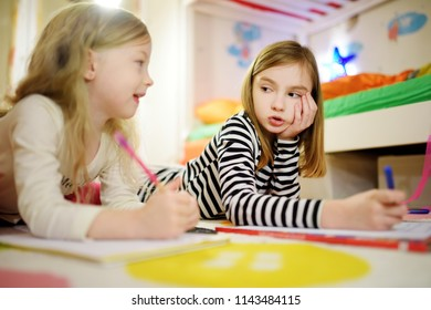 Two cute little sisters writing letters together at home. Older sister helping youngster with her homework. Education for kids.