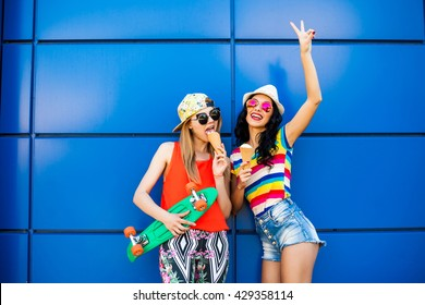 Two cute pretty awesome hipster girls, best friends, eat ice cream, wearing denim shorts, colorful leggings, bright T-shirts, rainbow, sunglasses, cap, hat, holding a long board, blue background