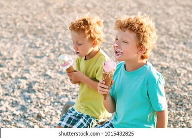 Two cute red curly boys brothers are extremely happy while getting dirty and eating ice cream on the summer beach