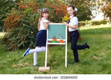 Two cute schoolgirls in school uniform with a chalkboard in the park. Children write on the easel blackboard.