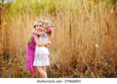 Two cute sisters girls holding each other tight with love in field of yellow dry grass