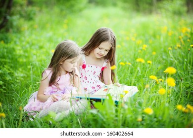 two cute sisters in the meadow reading a book