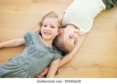 Two cute sisters on floor of children room smiling and having fun together