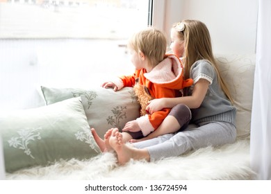 Two cute sisters sitting near window close to each other and playing