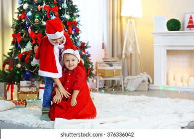 Two cute small brothers playing with Santa bag on Christmas decoration background