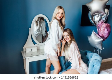 Two  cute ,smiling girlfriends  posing in apartament. Hen party.Balloons behind.