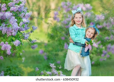 two cute smiling girls sisters lovely together on a lilac field bush all wearing stylish dresses and jeans coats.