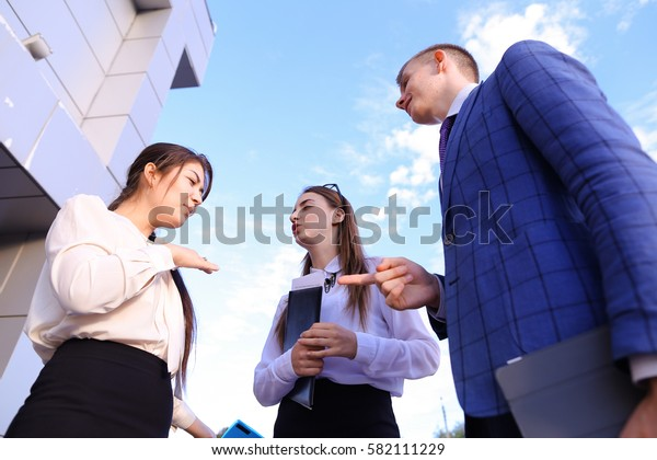 Two cute successful woman and elegant handsome male man successful young office workers, businessmen, students communicate, make deal, shake hands, talk on various topics, lead discussions, discuss