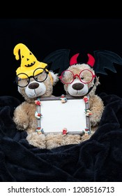 Two cute teddy bears dressed in Halloween costume sitting on black blanket holding wooden vintage photo frame with cartoon characters on it, against black wooden wall with copy space on top.