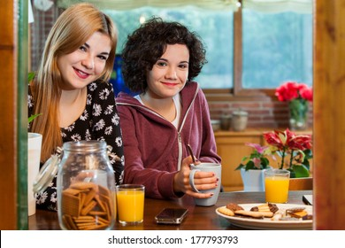 Two cute teen girl friends having tea and cookies together at home.