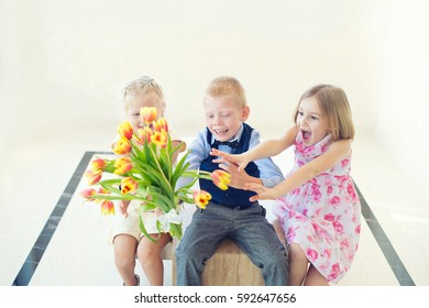 Two cute toddler girls fight for the flowers from a boy as a present on spring holiday