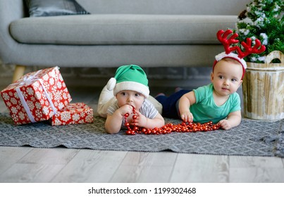 Two cute twin kids as Santa helpers for Christmas with present boxes, wearing reindeer antler headband and elf hat next to Christmas tree. Holiday season at home