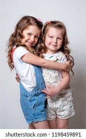 Two cute twins sisters hugging and smiling